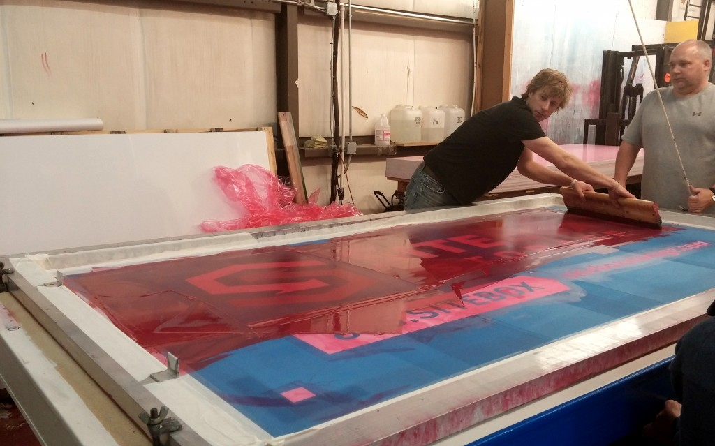 Greg, Tyson, and Kenny screen printing 4' x 8' aluminum signs. It's definitely a team effort!